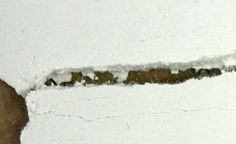 Fibers visible along a broken edge of a dried paper clay slab
