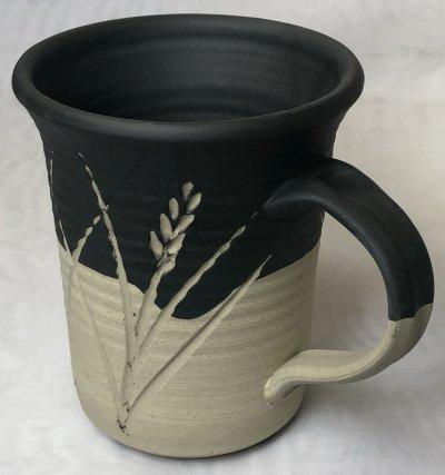 A buff stoneware vessel with black engobe
