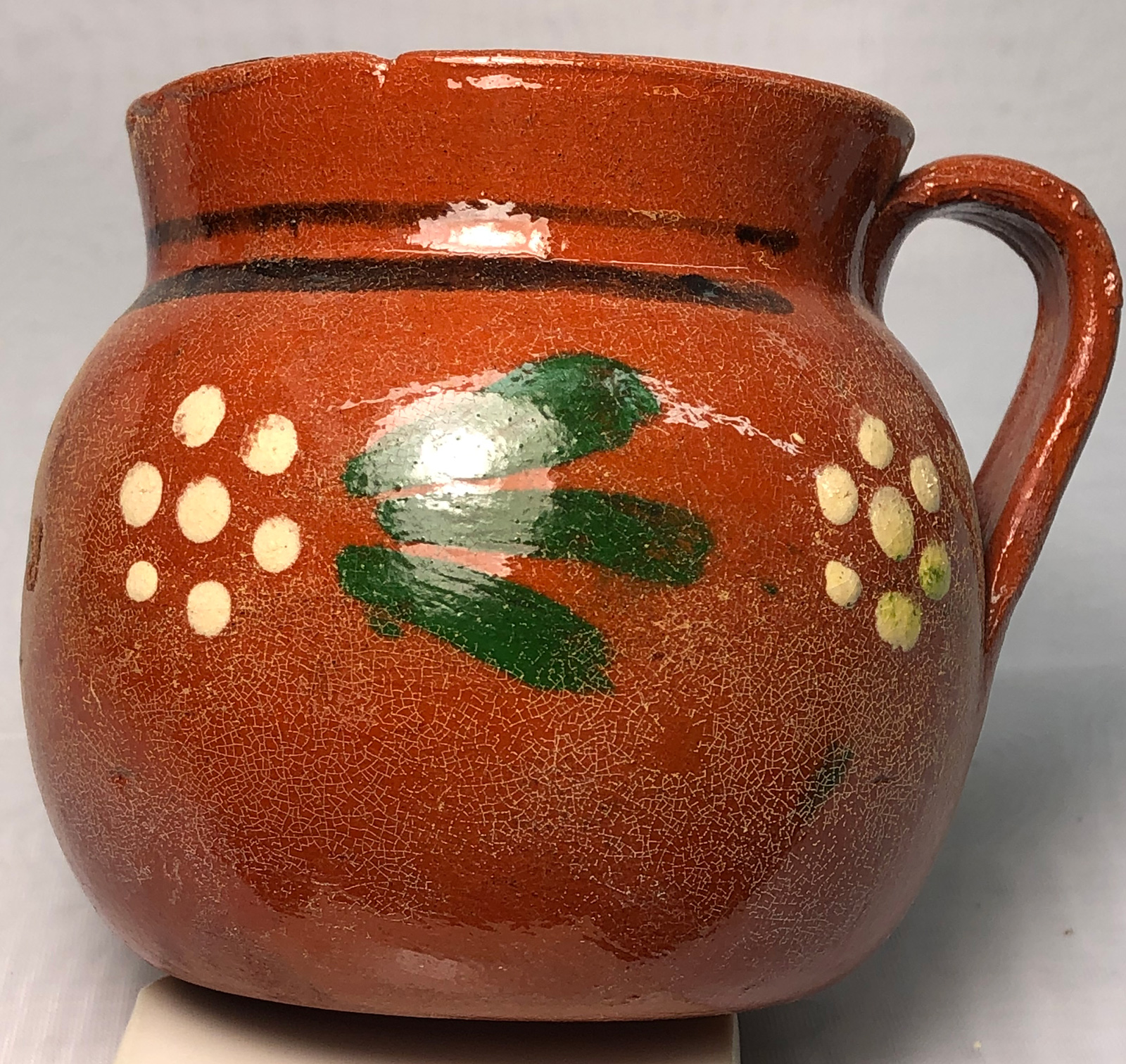 A terra cotta clear-glazed vessel with dissolved lead powder left behind on the surface