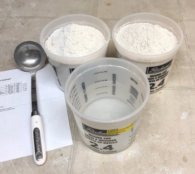 Two almost-full containers of clay powder, one half full of water