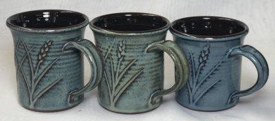 Three mugs with floating blue glazes