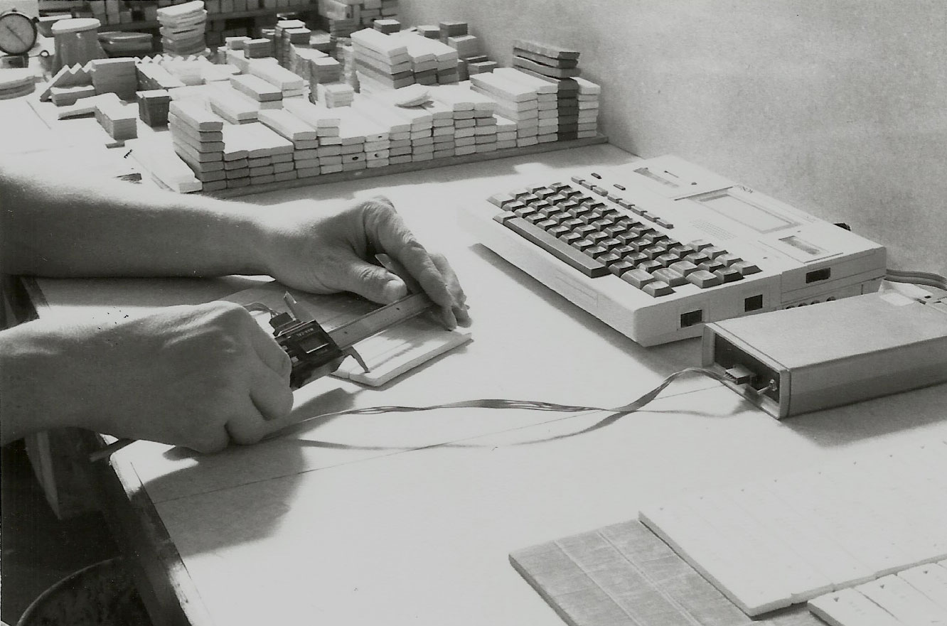 Measuring shrinkage/absorption test bars in 1983 at Plainsman Clays