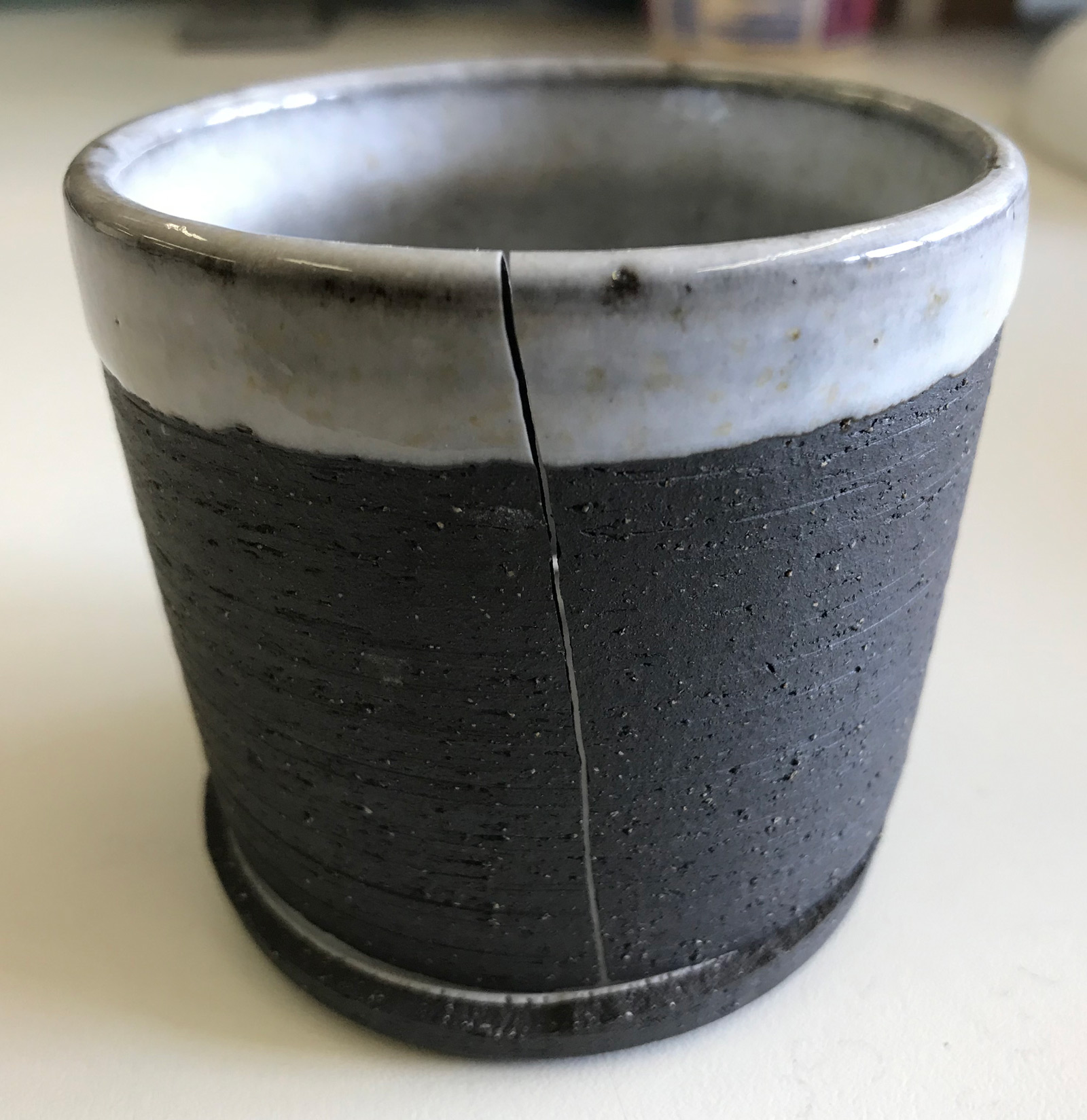 A glaze is pushing outward from the inside of this cup