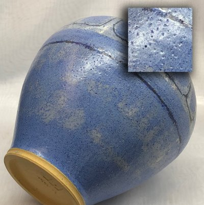 A cone 6 blue silky matte glazed vase with thousands of pinholes in the glaze