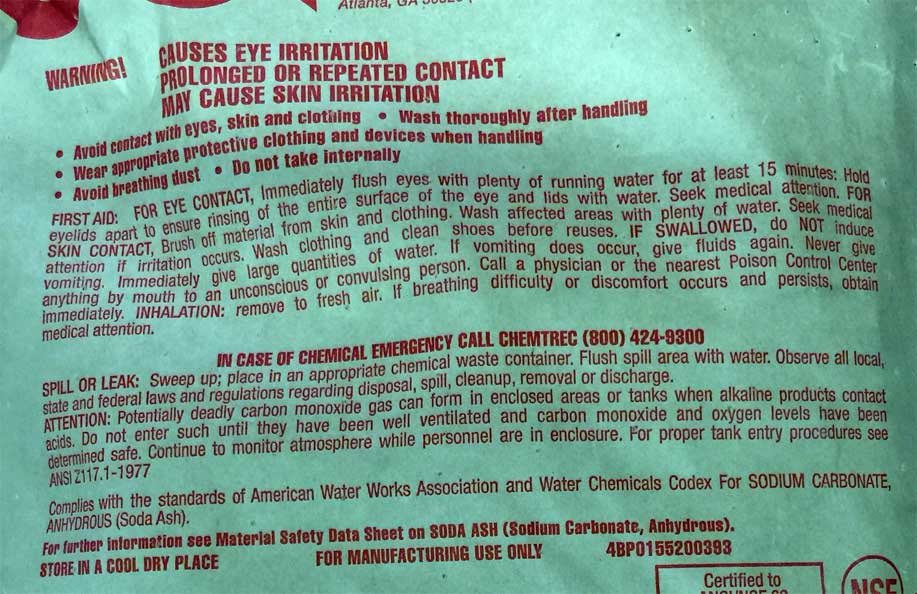 Health warnings on a bag of sodium carbonate (soda ash).