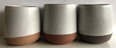 Three pottery mugs, two having glaze pinholes