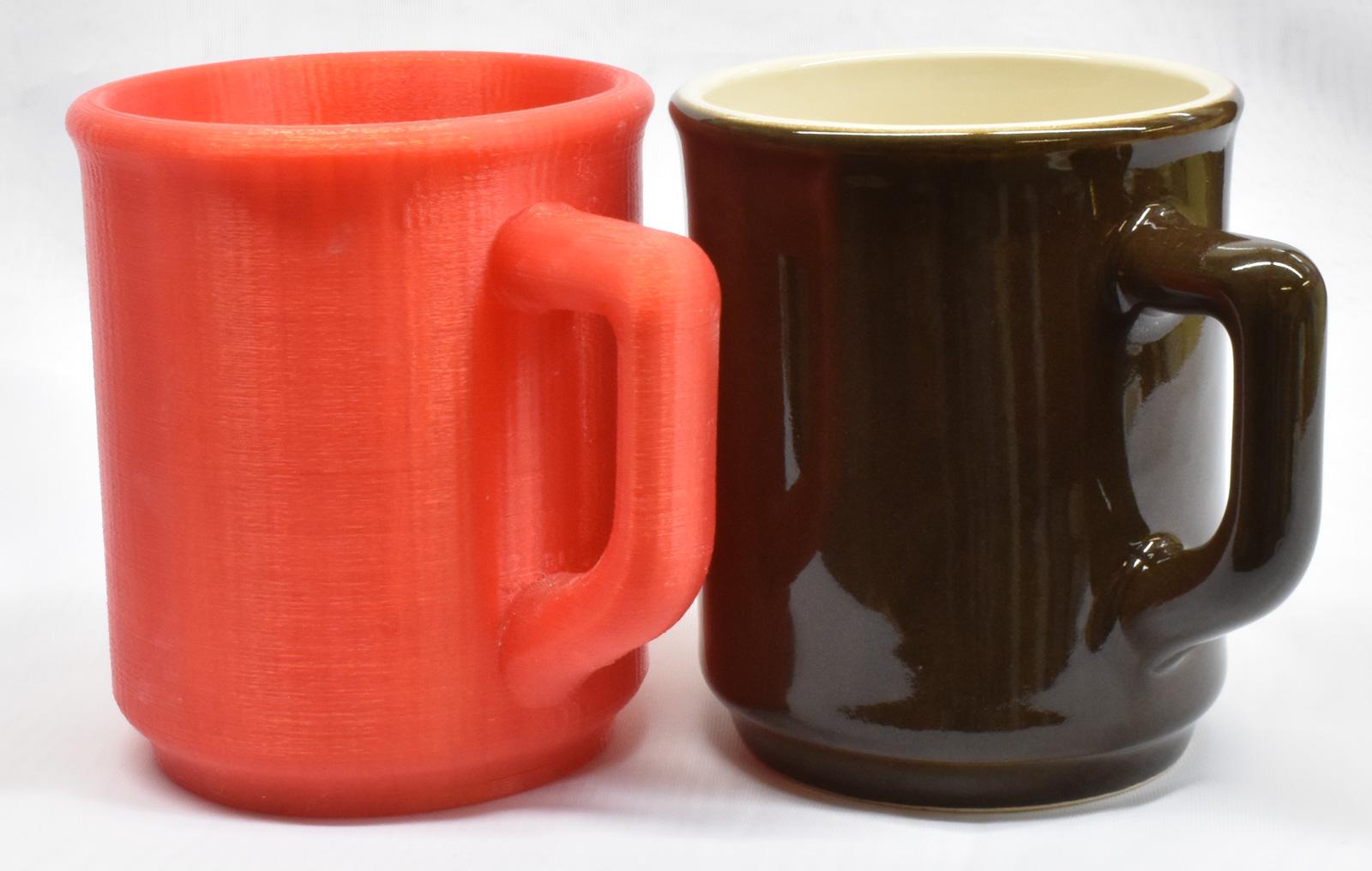 Final cast-jiggered cone 6 mug beside original 3D-printed mock-up