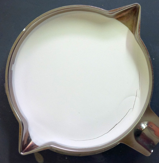 A tray, dried under a heat lamp, with a layer of powder glaze on the bottom