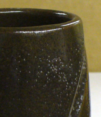 Why is this cone 10 oxidation iron-brown glaze pinholing?