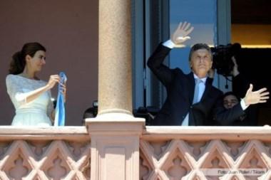Mauricio se contonea. la Primera Dama observa y sostiene la banda presidencial.