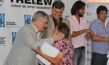 El exgobernador junto a Pérez Catán entregan el título a una vecina.