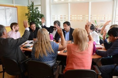 Sesión en una oficina. Los concejales levantan la mano en Presidencia, porque el recinto está en refacción.