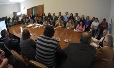 Todos en la mesa. El gobernador y varios de sus ministros en lo que fue una nueva licitación de viviendas para la ciudad de Rawson.