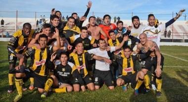 """¡Dale campeón! Un solo grito para todos los integrantes del plantel de Deportivo Madryn. Solitos, en el césped del """"Cayetano"""", celebrando el título."""