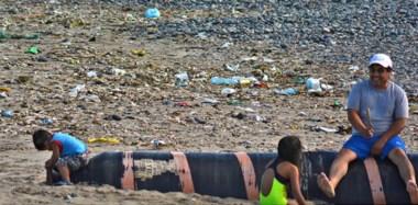 Mugre. No es un basural a cielo abierto: es una familia valletana tratando de disfrutar de Playa Unión en medio de residuos de todo tipo.