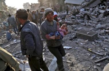 Un hombre corre con un bebé rescatado de entre los escombros de un edificio. Siguen  hallando cuerpos.