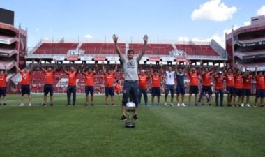 """Tagliafico, capitán del """"Rojo"""", adelante con la Copa, detrás el resto del plantel."""