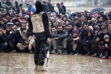 Los civiles iraquíes que huyen de la ciudad de Mosul se sientan bajo la lluvia, cuando las fuerzas iraquíes avanzan,
