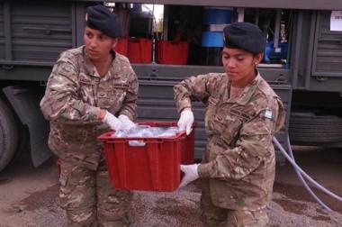 Delivery. Una postal de dos uniformadas distribuyendo los sachets de agua producidos en la planta móvil.