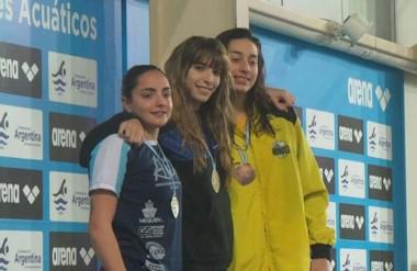La nadadora capitalina Julieta Lema (centro), con su medalla de oro, abrazando a las chicas del podio.