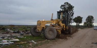 Máquinas municipales trabajando en un predio del barrio INTA  y desactivando, junto a las autoridades, un intento de usurpación de tierras.
