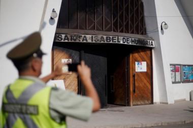Un carabinero toma fotografías del frente de una de las iglesias católicas atacadas este viernes.