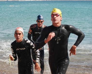 Los nadadores salen del agua y corren hacia la meta. Partieron desde el Parador Municipal hacia el centro.