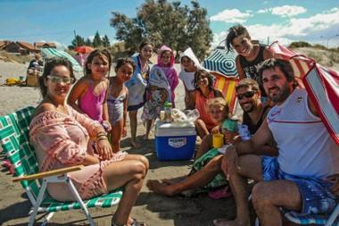 Luego del mediodía, las familias copan las playas madrynenses. Los adultos reposan y los niños van al agua.