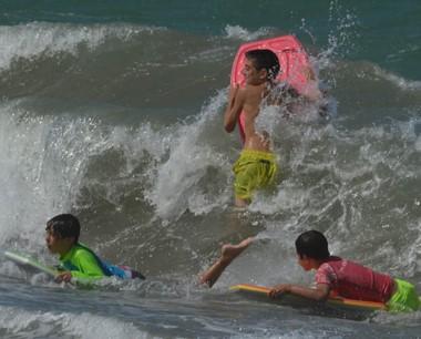 """Niños """"surfistas"""" experimentando el desafío de cabalgar olas."""
