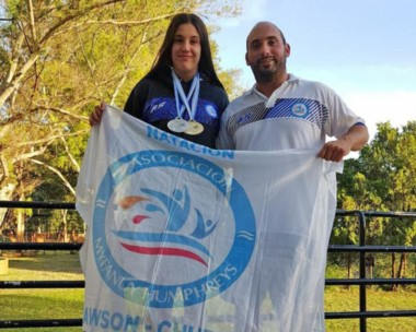María José Hildebrandt con su entrenador. En el cuello ostenta las dos medallas obtenidas en competencia.