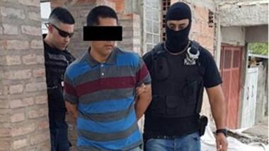 Uno de los presuntos delincuentes es llevado detenido por la Policía.