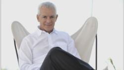 No son alas. Costantini, sentado en un sillón que genera una figura sugerente...