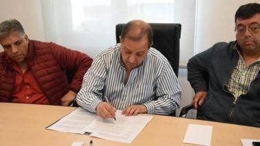 Rúbrica. Rodeado por los gremialistas, Linares firmó el acuerdo.