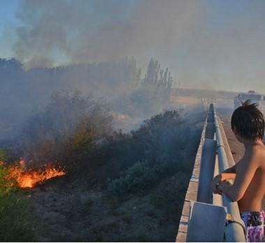 Una dotación de bomberos mientras combatía las llamas en una finca ribereña al sur de Trelew.