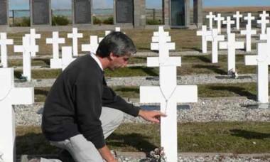 Julio  Aro en Malvinas arrodillado  ante las tumbas de ex compañeros.