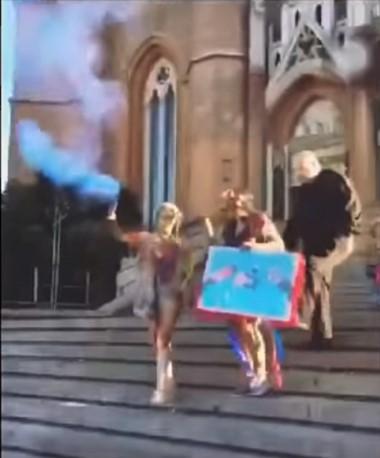 Captura del video en el preciso momento en que el cura le da una patada en la cola a la chica que festejaba su título en las escalinatas de la iglesia.