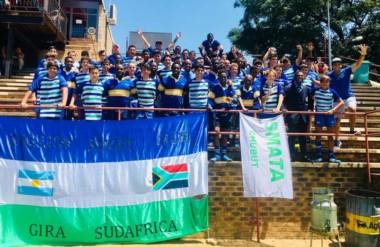 En las gradas del estadio, el Trelew RC con los chicos del club local. Debajo, la bandera trelewense.