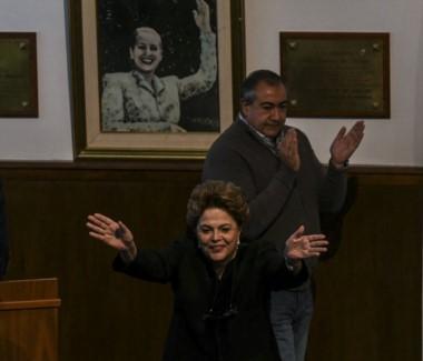El triunviro Héctor Daer aplaude a la ex presidenta del Brasil bajo la icónica imagen de la Abanderada de los Humildes...