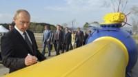 Putin estampa su firma durante la inauguración un gasoducto pintado con los colores de la bandera de Ucrania...