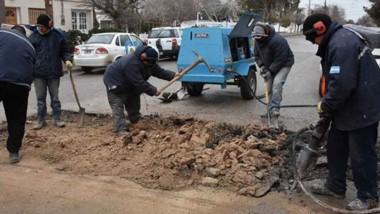 Reparación. Una postal de los empleados municipales arreglando uno de los múltiples baches de Trelew.