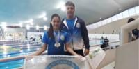 La nadadora Catalina Rodríguez con sus medallas, en compañía de su profesor Gabriel Radziviluk.