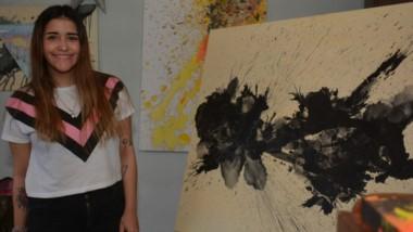 "Magalí junto a su obra titulada ""Hacia tu dirección"" (80x90 cm, tinta china diluida con alcohol, acrílico)."