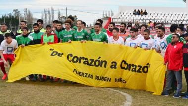 Ambos planteles posan con la bandera alusiva a Rubén Darío Vega.