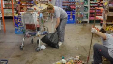 Empleadas del supermercado limpian los destrozos luego del saqueo relámpago.