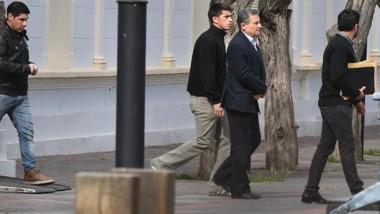 Peatonal. En una imagen inédita en la historia institucional de Chubut, el ministro Bortagaray deja Casa de Gobierno esposado y escoltado.