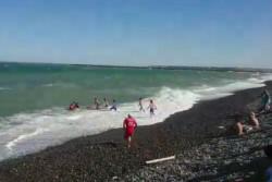 Los bañros rescatando a un bañista en la zona de la escollera de Playa Unión.