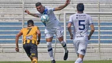 Luciano Sánchez despeja el balón ante el intento de  Gabriel Tellas y la mirada de Christian García, la figura del partido.  Brown perdió al final.