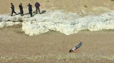 Escena. El cuerpo sin vida del joven en la costa madrynense y efectivos policiales trabajando en el lugar