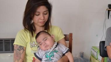 Benicio, el bebé de ocho  meses, junto  a sus padres que esperan de una respuesta concreta.