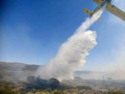 Un avión hidrante lanza su carga durante las tareas de combate al fuego. (fotos. F Bonancea).